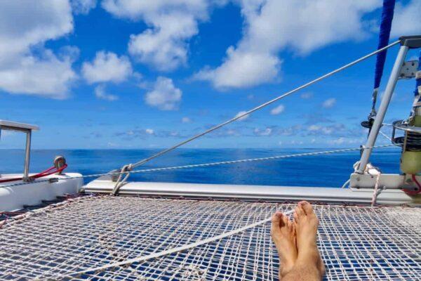 Füsse ausgestreckt auf dem Netz liegend mit Blick auf das ruhige Meer